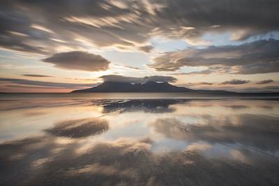 Dramatic sunset over Bay of Laig, Eigg towards Isle of Rum, Scotland.