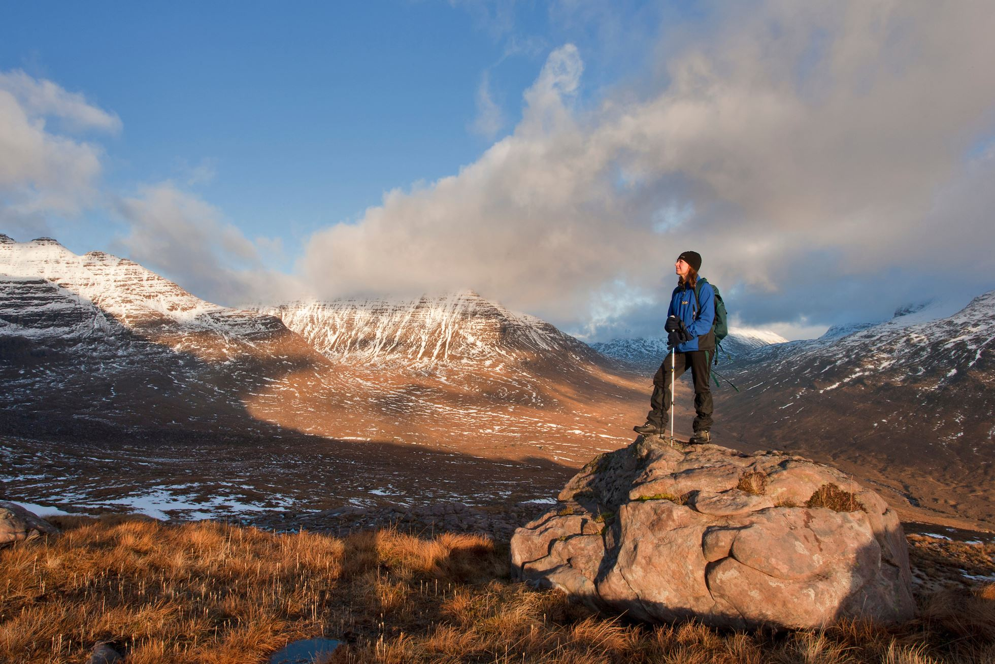 Woman (aged 40) on rock admiring the view on the route up Tom na Gruagaich, Beinn Alligin, Torridon, Scotland