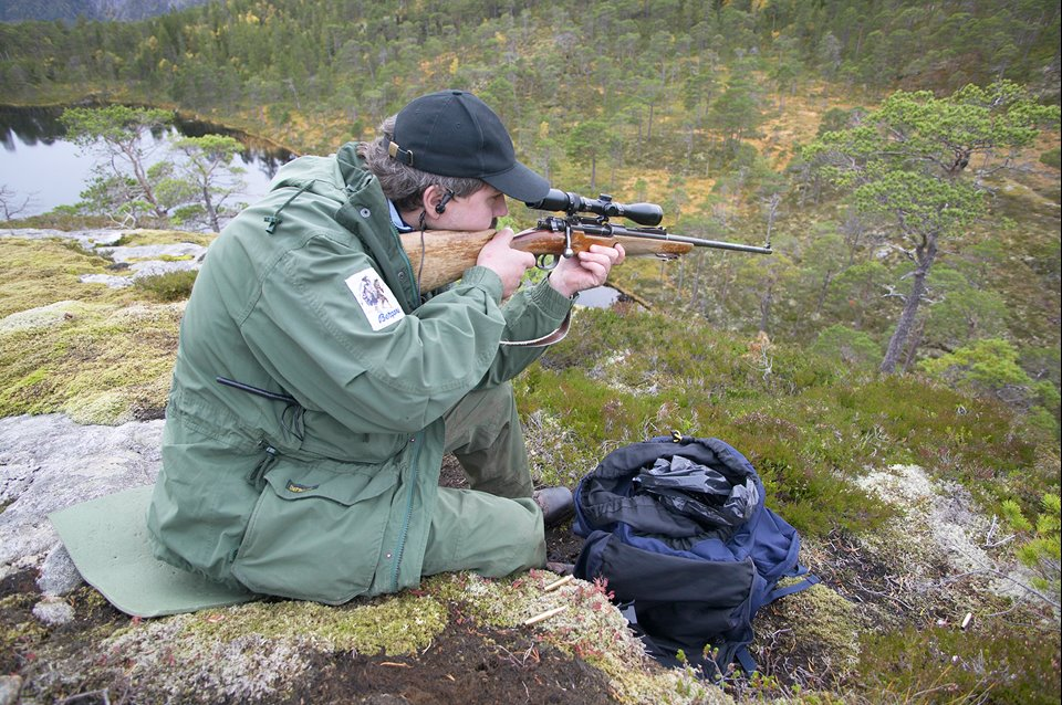Berndt Dahle, Norwegian hunter sat atop cliff in forest awaiting elk (moose) to be driven by dogs, Nord-Trondelag, Norway